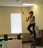 Tom juggles articles while on unicycle